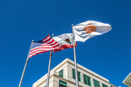 Cupertino, California, USA - August 15, 2016: close up of flags in front of Apple Headquarters with American Flag and flag with Apple icon at One Infinite Loop in Cupertino, Silicon Valley.