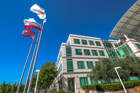 Cupertino, CA, USA - August 15, 2016: flags in front of Apple Headquarters with American Flag and flag with Apple icon. Apple is a multinational corporation that produces technology devise.