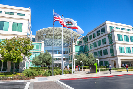 devise: Cupertino, CA, USA - August 15, 2016: people walk in front of the Apple world headquarters at One Infinite Loop. Apple is a multinational corporation that produces technology devise.
