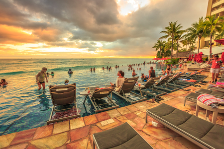 Waikiki, Oahu, Hawaii - August 20, 2016: people of infinity edge swimming pool, looking at the ocean sunset. Sheraton Waikiki Hotel in Waikiki Beach, Honolulu. Summertime relaxing in luxury resort.