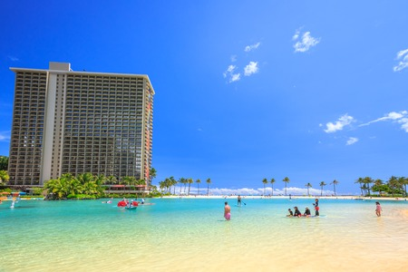 play popular: Waikiki, Oahu, HI - August 18, 2016: children play, swim, surf paddling in the lagoon at Hilton Hawaiian Village. The beach is one of more popular of Waikiki because offers a swimming area protected.