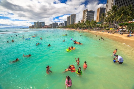 boogie: Waikiki, Oahu, HI - August 27, 2016: children play in the crowded Kuhio Beach called The Ponds because a concrete wall makes calm water and safe. Kuhio Beach is great for boogie boarding.