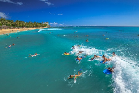 practiced: Waikiki, Oahu, Hawaii - August 27, 2016: Boogie boarding, bodyboarding also called, is a popular water sport practiced in Waikiki Beach near the Waikiki Pier at Queens Surf Beach in Honolulu.