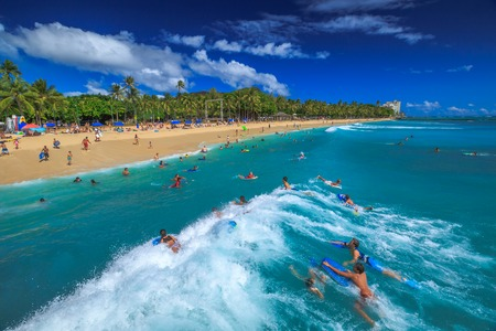 Waikiki, Oahu, Hawaii - August 27, 2016: Body boarding is a popular water sport in Waikiki area. One of best places to board is near the Waikiki Pier at Queens Surf Beach, a section of Waikiki Beach. Editorial