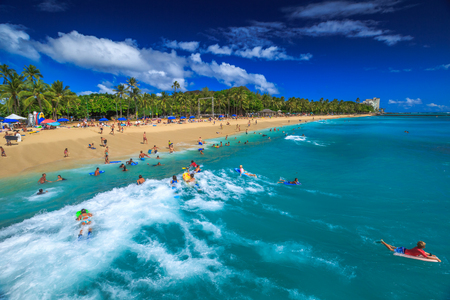 Waikiki, Oahu, Hawaii - August 27, 2016: Boogie boarding, bodyboarding also called, is a popular water sport practiced in Waikiki Beach near the Waikiki Pier at Queens Surf Beach in Honolulu.