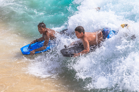bodyboarding: Waikiki, Oahu, Hawaii - August 27, 2016: Little boys on vacation having fun swimming on boogie board at Waikiki Beach in Honolulu. The body boarding is the most popular water sports of Waikiki. Editorial