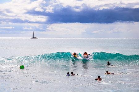 bodyboarding: Waikiki, Oahu, Hawaii - August 27, 2016: people on vacation having fun swimming on boogie board at Queens Surf Beach, a section of Waikiki Beach in Honolulu.