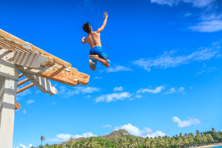 Waikiki, Oahu, Hawaii - August 27, 2016: a boy jumping off the Waikiki Pier between Kuhio Ponds and Queens Beach two sections of Waikiki Beach. On background, skyline of Diamond Head State Monument.