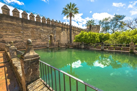 Decorative green pool around the military fortress The Alcazar de los Reyes Cristianos in a sunny day. Cordoba, Andalusia, Spain.
