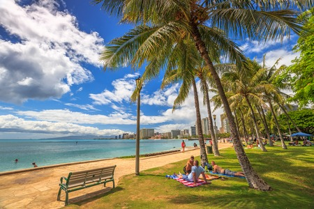 Waikiki ,Oahu, HI - August 27, 2016: people take the sun lying on the lawn fronting the popular Queens Beach section of Waikiki Beach. Wooden benches on Queens Beach boardwalk.