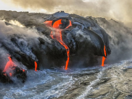 Kilauea Volcano in Hawaii Volcanoes National Park, also known Kilauea Smile because from 2016 seems to smile, erupting lava into Pacific Ocean, Big Island. Scenic sea view by boat. Imagens
