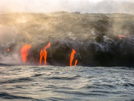 erupting: Kilauea Volcano in Hawaii Volcanoes National Park, also known Kilauea Smile because from 2016 seems to smile, erupting lava into Pacific Ocean, Big Island. Scenic sea view of lava by boats.