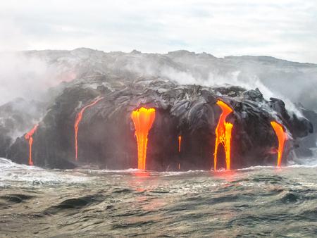 Cierre de Volcán Kilauea, Parque Nacional de Volcanes de Hawai, también conocida sonrisa Kilauea, porque a partir de 2016 parece sonreír, la erupción de lava en el Océano Pacífico, isla grande. Escénica vista al mar desde el barco. Foto de archivo