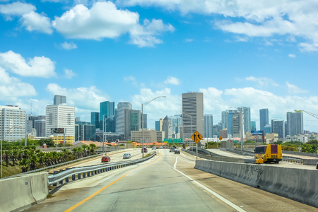 south miami: Miami, Florida, United States - April 8, 2012: cars driving on Miami Highway or Interstate 95, in the direction of South Miami. Downtown Miami skyline in the background.