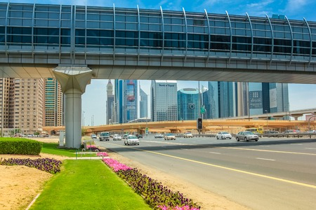 Dubai, United Arab Emirates - May 1, 2013: close up of Dubai Financial Centre Metro station and footbridge. Underground lines without a driver in the Dubai metro. Traffic on Sheikh Zayed Road. Editorial