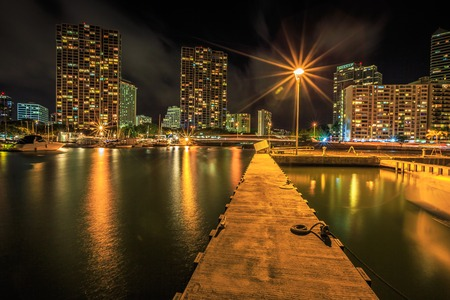 Jetty in Ala Wai Harbor, the largest yacht harbor of Hawaii. Honolulu Harbor skyline reflecting in the water at night near the popular Waikiki Beach, Oahu, Hawaii. Stock Photo