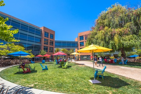 Mountain View, CA, USA - August 15, 2016: Google employees walking in relaxing area at Googles headquarters or Googleplex. Google is a multinational company specializing in Internet-related services.