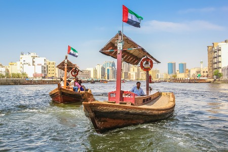 Dubai, United Arab Emirates - May 3, 2013: Traditional Abra ferries along Dubai Creek. The Creek divides the city into two main sections: Deira and Bur Dubai. On background, Twin Towers, old downtown.