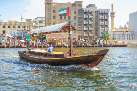bur dubai: Dubai, United Arab Emirates - May 3, 2013: a traditional dhow ferry along Dubai Creek. The Creek divides the city into two main sections: Deira and Bur Dubai, a historic district in Dubai.