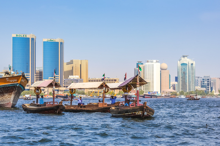 bur dubai: Dubai, United Arab Emirates - May 3, 2013: skyline view of Dubai Creek with traditional taxi boat activity. The creek divided the city in Deira and Bur Dubai. On background, Twin Towers, old downtown.