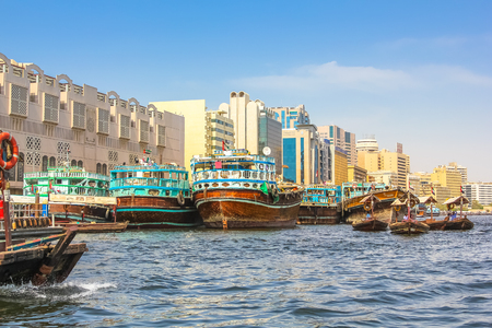 Dubai, United Arab Emirates - May 3, 2013: traditional wooden boats docked on the Bay Creek in United Arab Emirates. On background the skyline of Deira, the old downtown of Dubai.