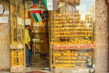 gold souk: Dubai, UAE - May 3, 2013: jewelers in a typical gold shop in Old Deira. The Grand Souk Deira is an entire neighborhood of narrow streets and dark and bottege selling spices, gold, perfumes.