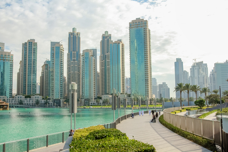 People walking along the waterfront promenade that runs along the Burj Khalifa Lake and the Burj Khalifa. On background, the Old Town Island and the Dubai Mall in Downtown Dubai. Stock Photo