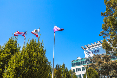web portal: Sunnyvale, California, United States - August 15, 2016: flags in front of Yahoo Headquarters with American Flag and flag with Yahoo icon in the blue sky.