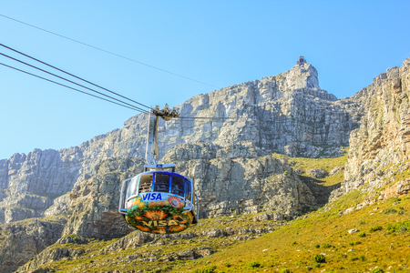 table mountain national park: Cape Town, South Africa - January 11, 2014: the cable cars beams to the top of the famous Table Mountain National Park. Aerial Cableway popular tourist attraction in Cape Town in the blue sky. Editorial