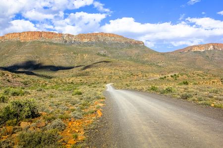 Adventure in African desert. Dirt mountain road in the blue sky, Karoo National Park in the summer, Western Cape province of South Africa. Dry season.