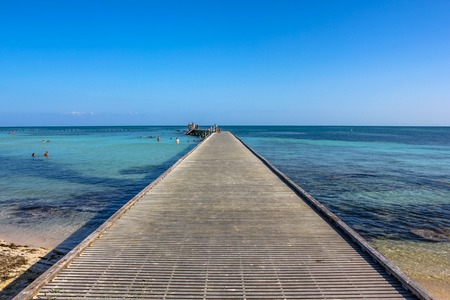 Wooden path at Higgs Beach, a popular Key West beach in Florida, United States. Infinity and freedom concept.