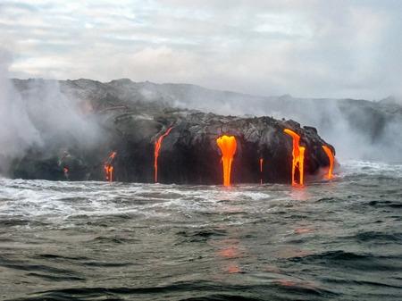 Escénica vista al mar desde el barco del volcán Kilauea en Hawaii Volcanoes National Park, mientras que la erupción de lava en el Océano Pacífico, Big Island, Hawai.
