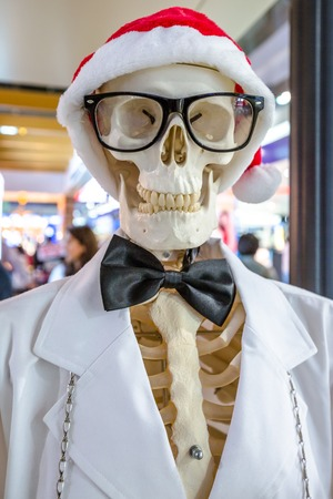 Portrait of a skeleton wearing a Santa Claus hat, black glasses and a white jacket with black papillon. Conceptual christmas holidays.
