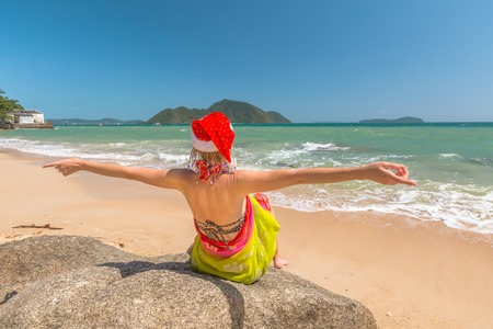 ka: Christmas in the tropics. Beautiful woman with red Santa Claus hat enjoy and catching tan on rocks in tropical Laem Ka Beach for the Christmas holidays in Phuket, Thailand. Christmas vacation concept. Stock Photo