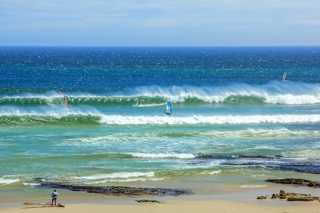 Scarborough Beach. Windsurf in Cape Town, South Africa. Surfer tries to take a high and powerful wave. Atlantic coast, Cape Peninsula.