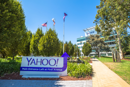 web portal: Sunnyvale, California, United States - August 15, 2016: flags in front of Yahoo Headquarters main entrance with American Flag and flag with Yahoo icon.