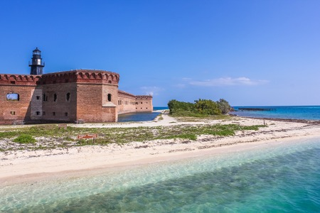 dry tortugas: South Coaling Dock Ruins in Fort Jefferson, a historical military fortress, dominated by Garden Key Lighthouse, on Dry Tortugas National Park, Florida, United States.