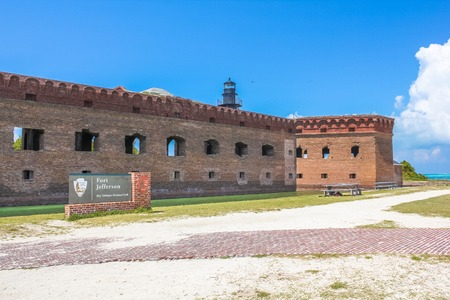 dry tortugas: The entrance of Fort Jefferson, a historical military fortress, dominated by Garden Key Lighthouse, on Dry Tortugas National Park, Florida, United States.
