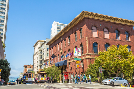 San Francisco, California, United States - August 17, 2016: two Cable Car ride for California and Powell streets, where the three lines intersect in a set double crossovers. People crossing the street