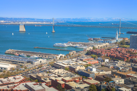 Aerial panorama of San Francisco Embarcadero and Oakland Bridge, from top of Coit Tower on sunny day. Telegraph Hill, California, United States. Stock Photo