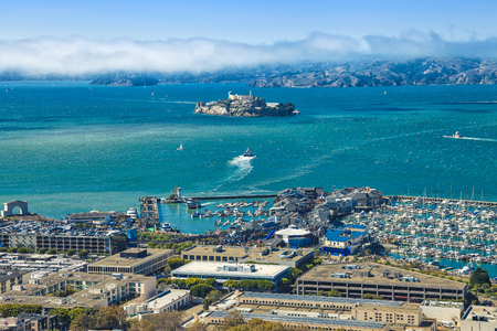 Aerial view of Alcatraz Island, Hyde Street Pier in Fishermans Wharf and Maritime National Historical Park, from top of Coit Tower on sunny day. San Francisco, California, Unites States.
