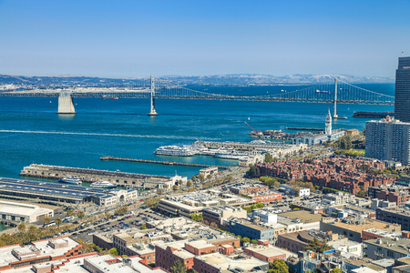 Aerial cityscape of San Francisco Embarcadero and Oakland Bridge from top of Coit Tower on sunny day on Telegraph Hill, California, United States. Stock Photo