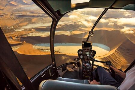 ヘリコプターのコックピットを飛ぶ Deadvlei、小屋の中のパイロットの腕とコントロール ボード、ナミビア、ナミブ ウクルフトパ国立ソーサス フラ