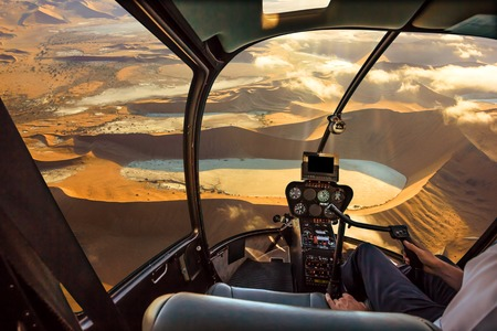 Helicopter cockpit flies in Deadvlei, Sossusvlei desert in Namib Naukluft National Park, Namibia, with pilot arm and control board inside the cabin.