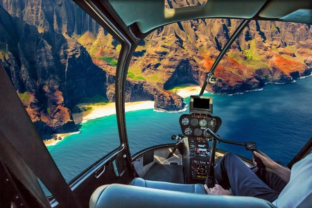Helicopter cockpit flies in Na Pali coast, Kauai, Hawaii, United States, with pilot arm and control board inside the cabin.