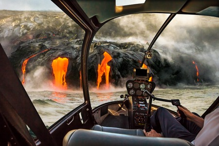 Helicopter cockpit flies in Kilauea Volcano, Big Island, Hawaii, United States by sunset, with pilot arm and control board inside the cabin.