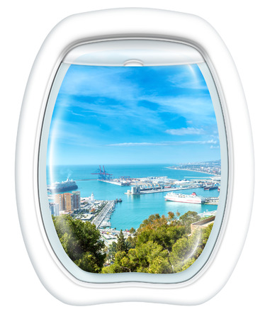 Plane window on port of Malaga from the Gibralfaro Castle, Andalusia, Spain, from a plane through the porthole. Copy space.