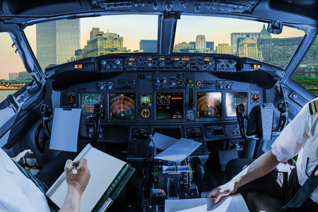 arms trade: Airplane cockpit flying on New York City with World Trade Center and Twin Towers, Manhattan, United States, with pilots arms and blank white papers for copy space. Stock Photo
