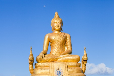 The golden Buddha made of 22 tons of brass and 12 meters high, inside the temple of popular and largest Bid Buddha in Chalong, Phuket, Thailand in the blue sky. Peace and meditation concept.