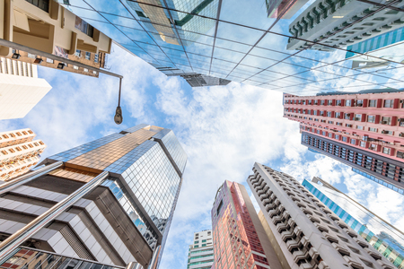 Panoramic wide angle view and perspective to steel light background of glass high rise buildings. Causeway Bay, the popular luxury shopping district in Hong Kong Island.